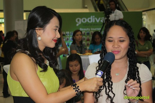 claudette centeno talks with an audience during Godiva launching